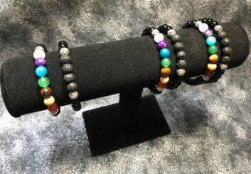 6 chakra bracelets on a black stand