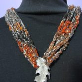 crochet necklace made from autumn-colored ladder yarn with a silver leaf brooch