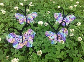 4 multi-colored crocheted butterflies lying on a field of clover