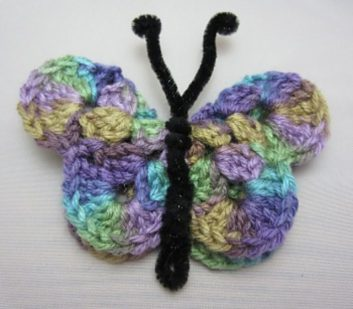 a crocheted butterfly made from pastel rainbow yarn, 3rd pattern
