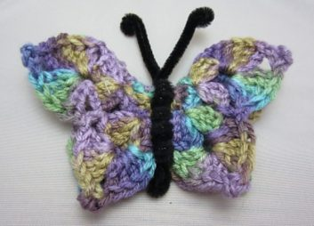 a crocheted butterfly made from pastel rainbow yarn, 4th pattern