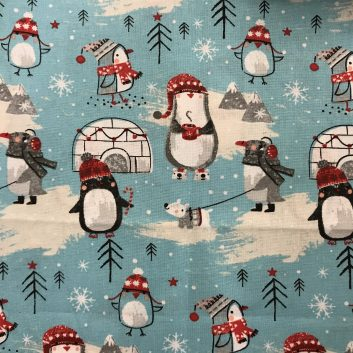fabric with enguins wearing hats with igloos and snow on blue background